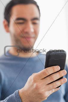 Happy casual man sending a text message