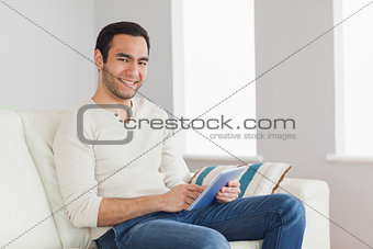 Cheerful casual man using his tablet