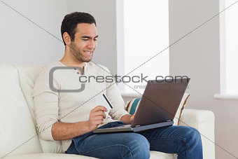 Cheerful handsome man using his credit card to buy online