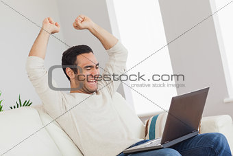 Victorious handsome man looking at his laptop