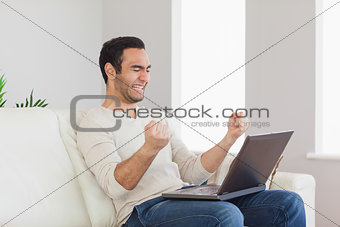 Successful handsome man looking at his laptop