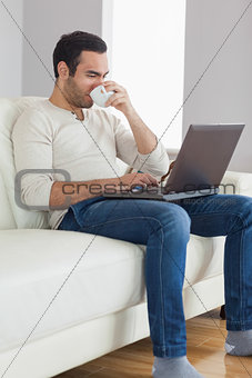 Relaxed attractive man drinking coffee while working on his laptop