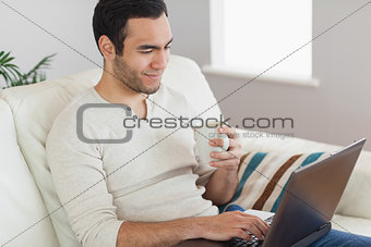 Calm attractive man drinking coffee while working on his laptop