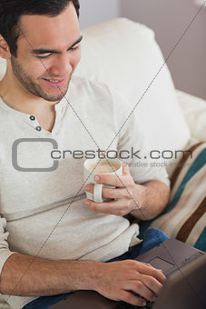 Calm attractive man drinking coffee while using his laptop