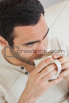 Thoughtful handsome man drinking coffee while relaxing on sofa