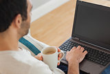 Brown haired man holding coffee using his laptop