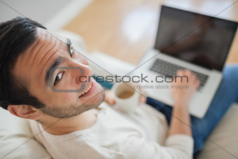 High angle view of smiling young man using his laptop