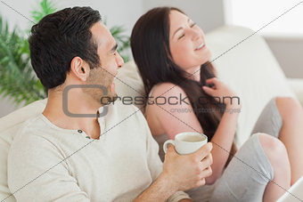 Cheerful couple relaxing together on sofa