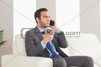 Serious businessman on the phone sitting on cosy sofa