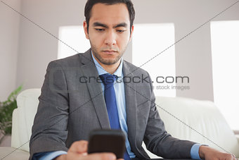 Serious businessman sending a text message