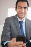 Smiling businessman sending a text message