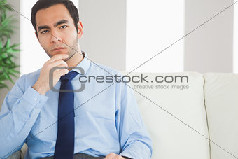 Thoughtful classy businessman sitting on cosy sofa