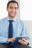 Smiling classy businessman using tablet pc