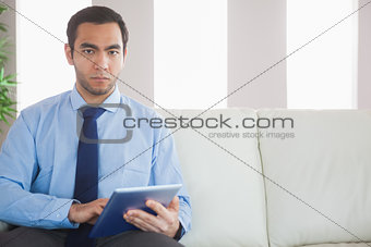 Unsmiling classy businessman using tablet pc