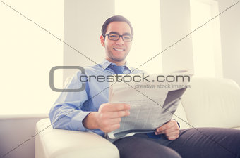 Pleased man looking at camera and holding a newspaper sitting on a sofa