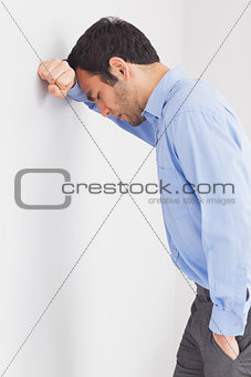 Worried man leaning his head against a wall