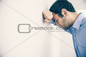 Depressed man leaning his head against a wall