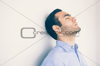 Thoughtful man leaning against a wall