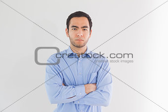 Serious man standing with arms crossed and looking at camera