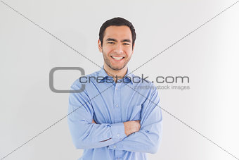 Smiling man standing with arms crossed and looking at camera