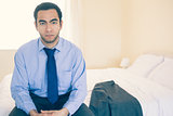 Frowning man looking at camera sitting on his bed