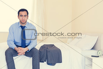 Stern man looking at camera sitting on his bed