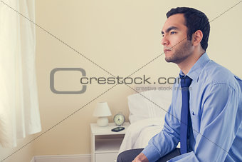 Unhappy man looking away sitting on his bed