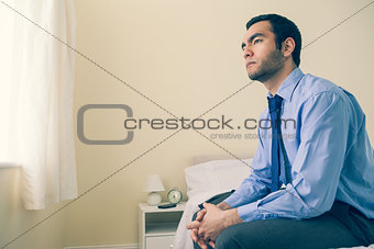 Thinking man looking away sitting on his bed