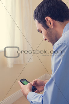 Close up of a man using a mobile phone sitting on a bed