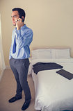 Serious man calling someone with a mobile phone and looking away