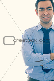 Smiling man looking at camera standing in front of a window
