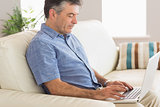 Thinking man sitting on sofa using laptop