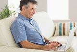 Smiling man sitting on a sofa using a laptop