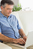 Concentrated man sitting on a sofa typing on a laptop