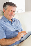 Smiling man sitting on a sofa using a tablet pc