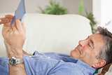 Smiling man laying on a sofa using a tablet pc