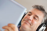 Smiling man listening music and using a tablet pc