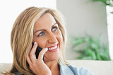 Smiling woman calling someone with her mobile phone