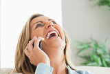 Laughing woman calling someone with her mobile phone