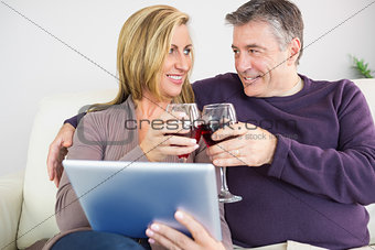 Happy couple toasting with wine sitting on a sofa