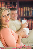 Happy couple drinking coffee sitting on a sofa