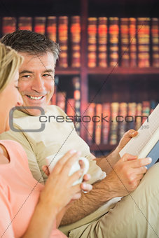 Happy couple reading books and drinking coffee in a reading room