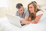 Happy couple lying on a bed watching a laptop