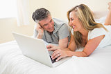 Laughing couple lying on a bed using a laptop