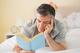 Concentrated man reading a book on his bed