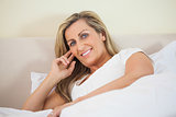 Smiling woman lying on a bed looking at camera