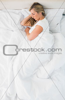 Sleeping woman lying on her bed