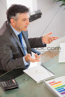 A businessman sitting at his desk explaining something