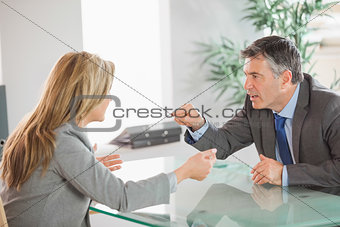 Two angry co workers arguing in an office