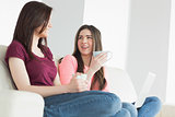 Two laughing girls sitting on a sofa enjoying a beverage and holding a laptop